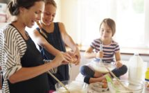 Shot of two little girls baking with their mother in the kitchen