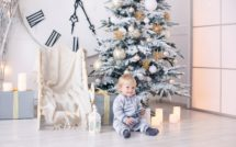 baby boy in pajamas with stars celebrates Christmas